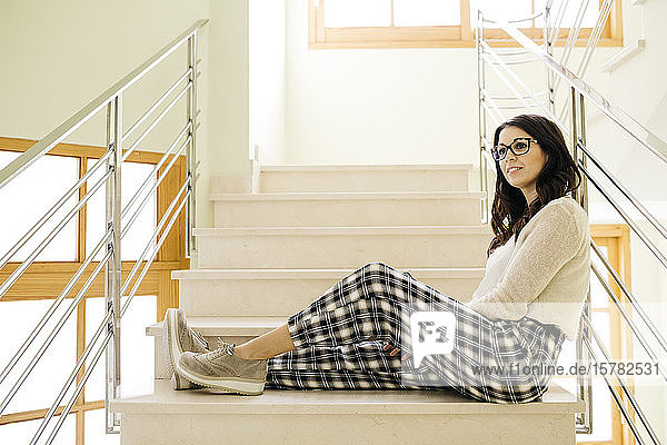 Young woman sitting relaxed on stairs