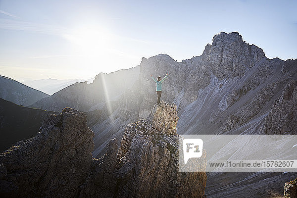 Hiker standing on rock spur  looking at the mountains
