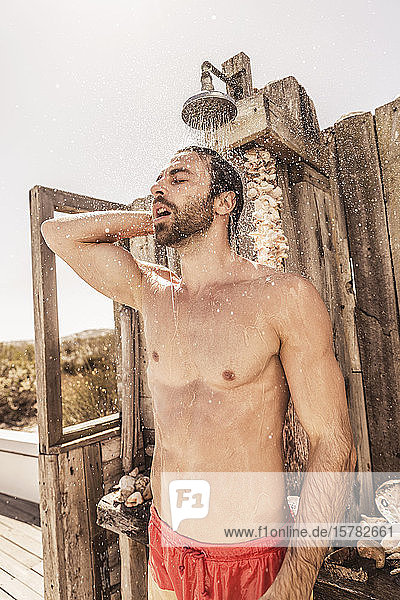 Young man taking a shower in an outside shower