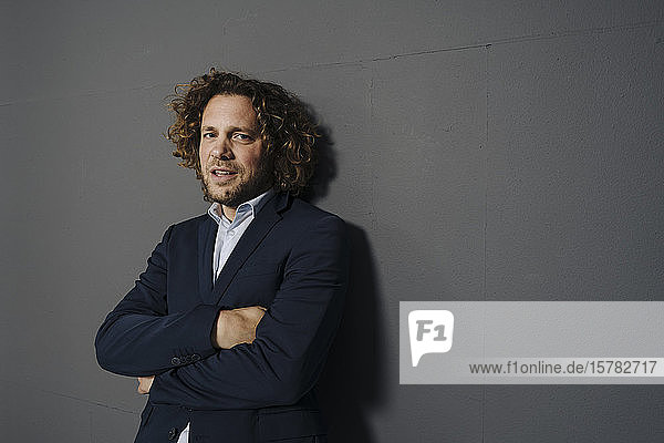 Porträt eines selbstbewussten Geschäftsmannes an grauer Wand