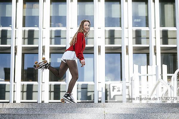 Blonde Frau balanciert mit Rollschuhen