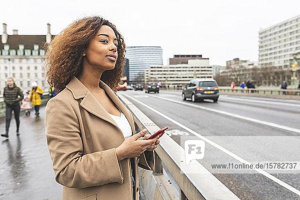 Junge Frau mit Handy auf einer Straße in der Stadt  London  Großbritannien