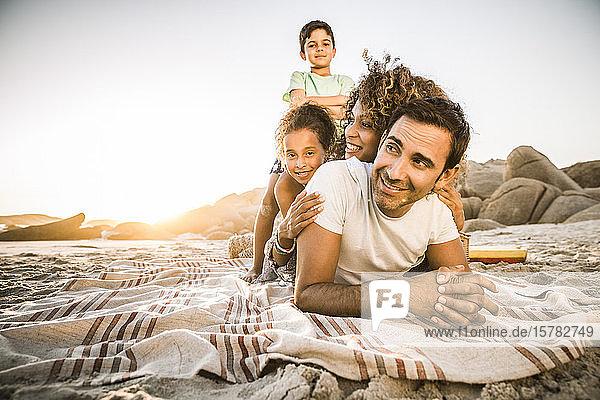 Glückliche Familie amüsiert sich bei Sonnenuntergang am Strand