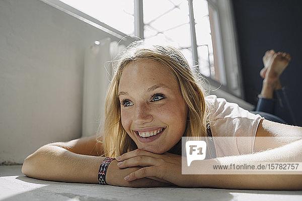 Porträt einer glücklichen blonden jungen Frau auf dem Boden liegend