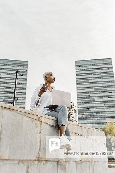 Lässige Geschäftsfrau  die in der Stadt sitzt und einen Laptop benutzt
