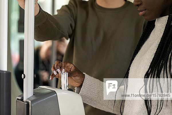 Close-up of woman validating ticket in tramway