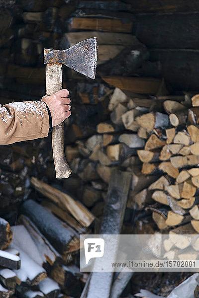 Männerhand hält im Winter eine Axt vor einem Brennholzstapel