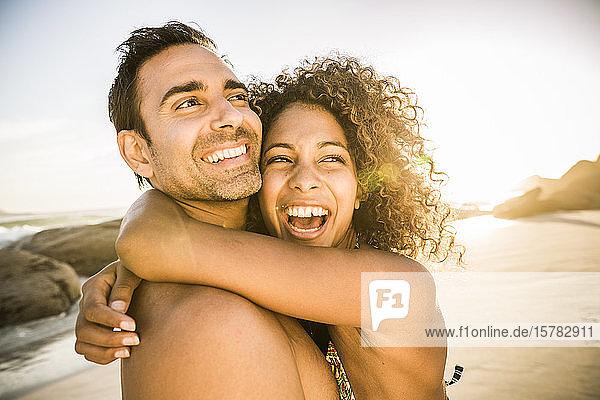 Sorgenfreies Paar umarmt sich am Strand bei Sonnenuntergang
