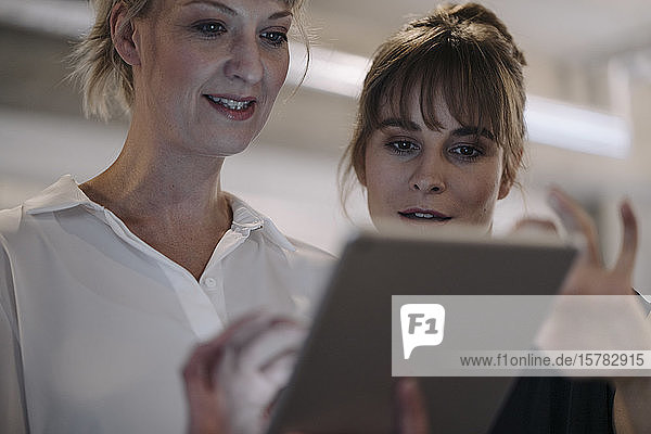 Two businesswomen having a meeting in office sharing a tablet