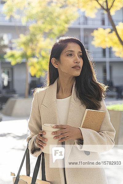 Junge Frau mit Buch und Kaffee zum Mitnehmen in der Stadt  die sich umsieht