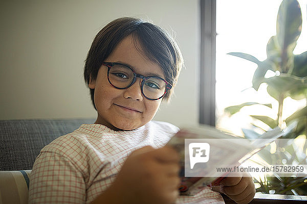 Portrait of smiling boy with glasses reading book at home