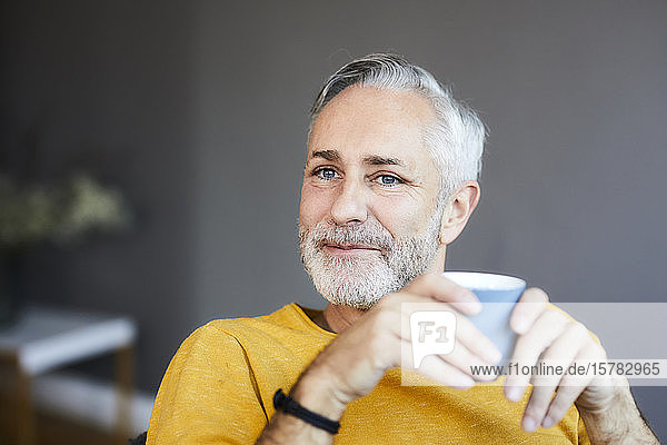 Portrait of smiling relaxed mature man at home with cup of coffee