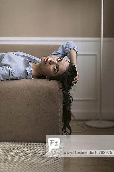 Porträt einer schönen jungen Frau  die zu Hause auf der Couch liegt