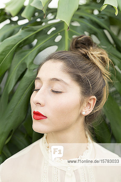 Porträt einer jungen Frau mit roten Lippen und entspannt geschlossenen Augen