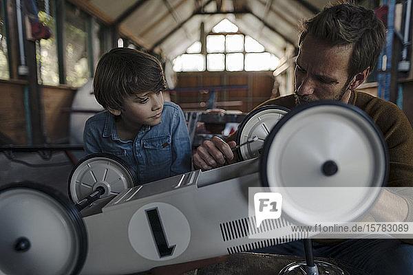 Vater und Sohn reparieren Spielzeugauto in der Scheune