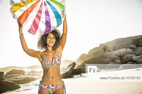 Glückliche junge Frau hält aufblasbaren Ball am Strand