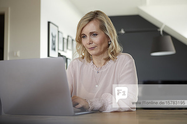 Blond woman using laptop at home