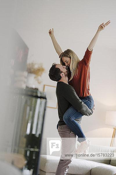 Mann hebt und umarmt seine jubelnde Frau