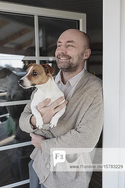 Porträt eines entspannten Mannes mit Hund auf den Armen  der an der offenen Terrassentür seines Hauses steht