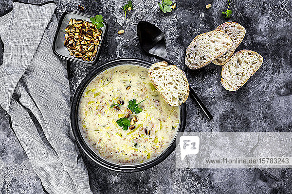 Bowl of vegetarian leek soup with cheese  pine nuts and parsley