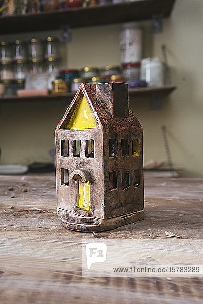 Tiny ceramic house on workbench in a pottery