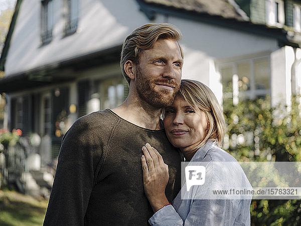 Porträt eines lächelnden Paares  das vor seinem Haus steht