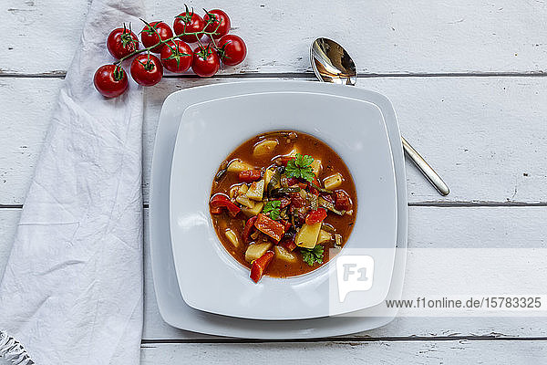 Plate of vegan goulash withpotatoes  bell pepper  tomatoes  leek and parsley