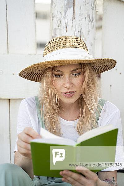 Junge Frau verbringt einen Tag am Meer  liest ein Buch am Strand