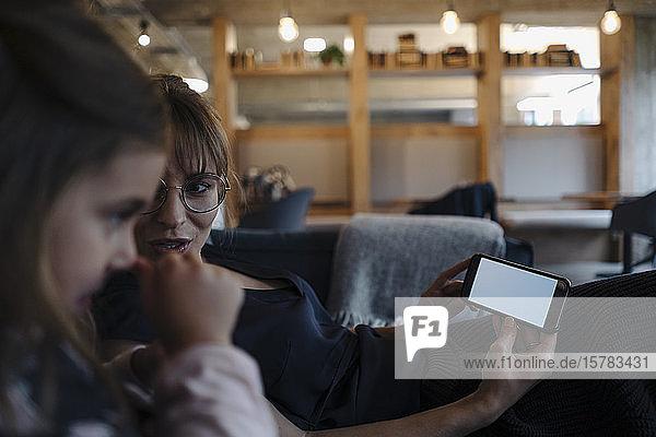 Frau und Mädchen sitzen im Büro auf der Couch und benutzen ein Smartphone