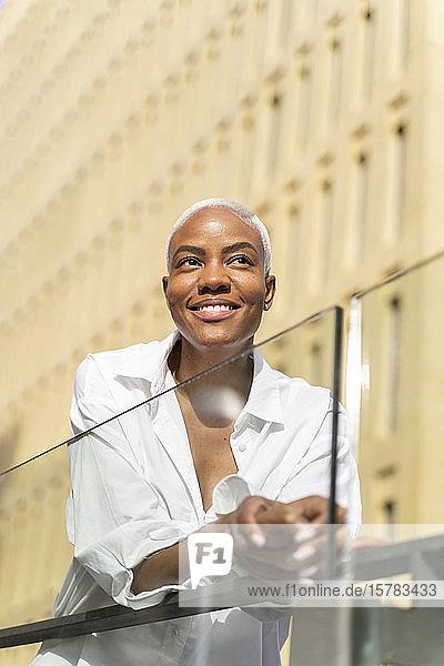 Attraktive Geschäftsfrau lehnt sich in der Stadt an ein Geländer