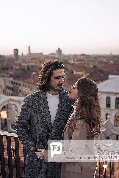 Zärtliches junges Paar auf einem Balkon über der Stadt Venedig  Italien