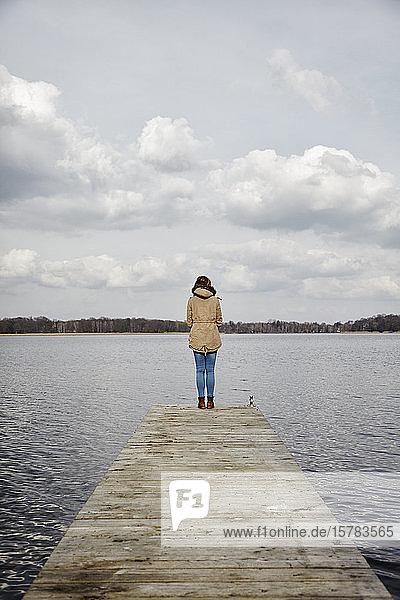 Rückenansicht einer Frau  die auf einem Steg steht und auf den See schaut