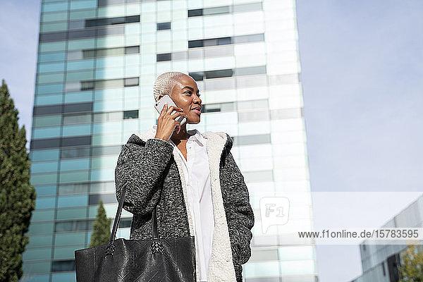 Stilvolle Geschäftsfrau  die in der Stadt pendelt und ein Smartphone benutzt