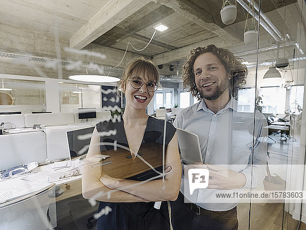Portrait of happy businessman and businesswoman behind a glass pane in office