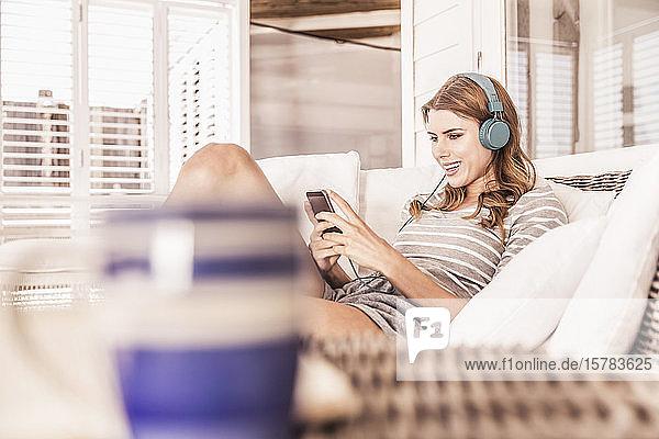 Junge Frau entspannt sich auf einer Veranda mit Smartphone und Kopfhörern