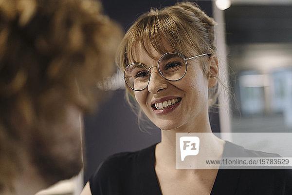 Porträt einer lächelnden Geschäftsfrau  die einen Geschäftsmann im Büro ansieht