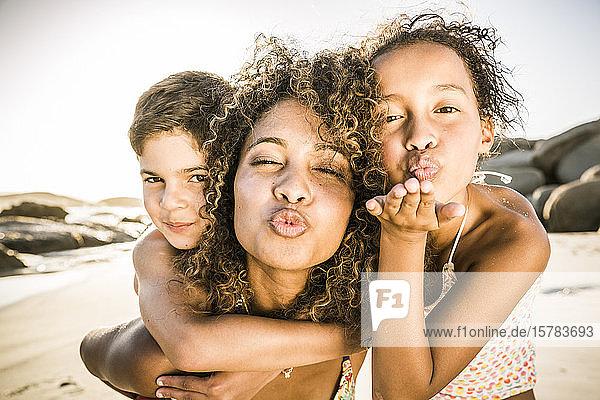 Porträt einer Mutter mit ihren beiden Kindern bei der Unterhaltung am Strand