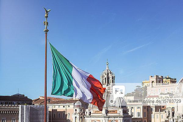 Italien  Rom  die italienische Flagge flattert gegen den klaren blauen Himmel und die Kuppel von Santa Maria di Loreto