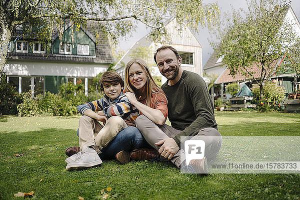 Glückliche Familie sitzt auf dem Rasen in ihrem Garten
