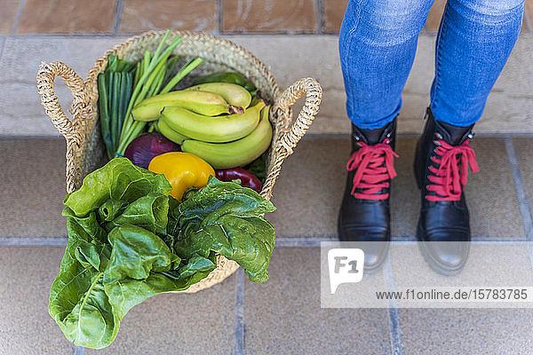 Frau steht an Korb voller Bio-Obst und -Gemüse Frau steht an Korb voller Bio-Obst und -Gemüse