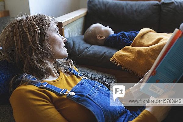 Frau liest Buch im Wohnzimmer  während der kleine Sohn schläft