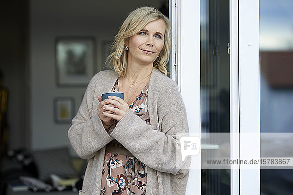 Blond woman leaning against balcony door at home