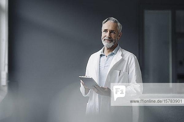 Portrait eines Arztes mit digitalem Tablett aus der Ferne