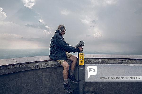 Älterer Mann sitzt auf der Wand des Beobachtungspunktes und schaut auf Sicht