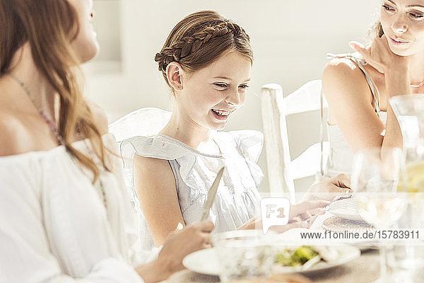 Glückliches Mädchen und zwei Frauen essen zusammen zu Mittag