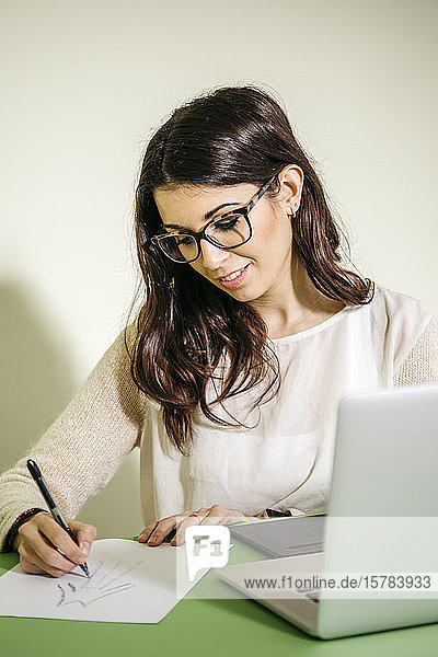 Young woman sitting at desk in office drawing on paper