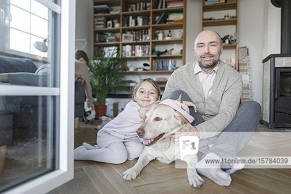 Porträt eines Vaters  der mit seiner kleinen Tochter und dem Hund zu Hause auf dem Boden sitzt