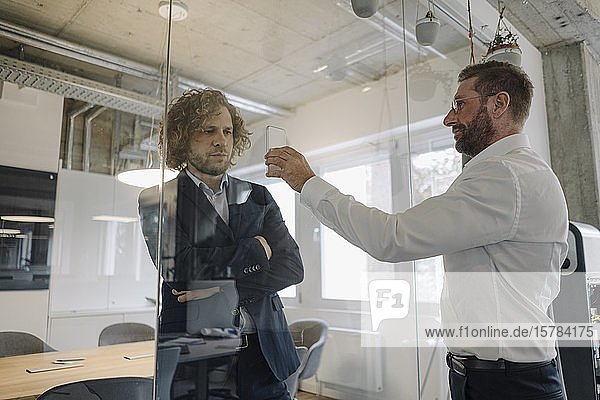 Geschäftsmann zeigt seinem Kollegen hinter einer Glasscheibe sein Handy