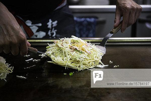 Japan  Kyoto  Nahaufnahme des Küchenchefs bei der Zubereitung von Okonomiyaki im Restaurant