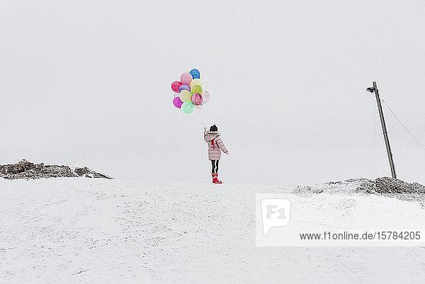 Rückenansicht eines Mädchens mit Ballons  das im Winter auf einem schneebedeckten Hügel steht
